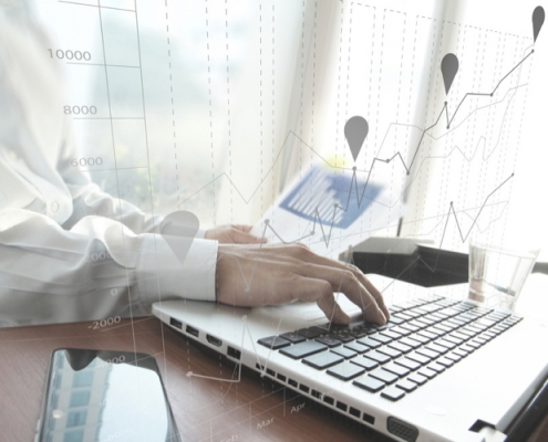 business man hand working on laptop computer on wooden desk as concept and graph business diagram